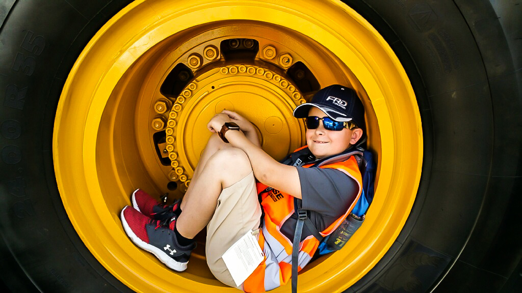 Caden Mashburn sitting inside the wheel of a B60E